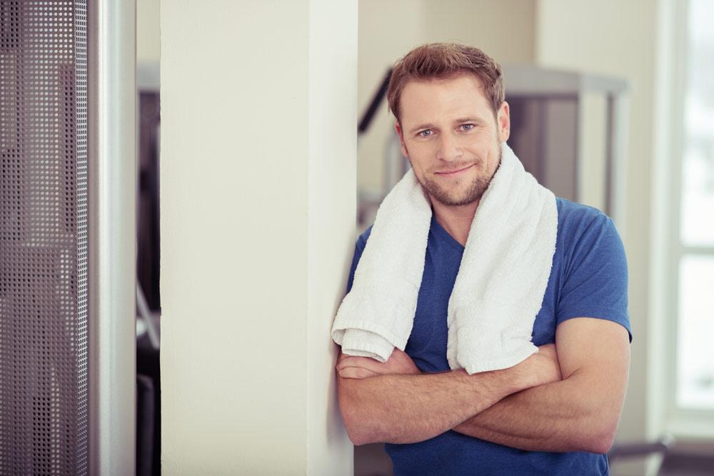 Mann lehnt an einer Säule - pro-fitness-discounter